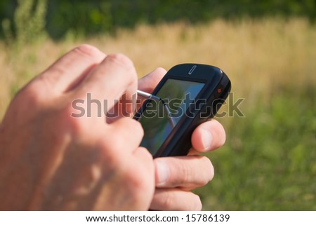 making notes on PDA in a wheat field - stock photo