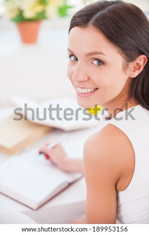 Making notes. Rear view of young beautiful woman writing something in her note pad and smiling at camera - stock photo