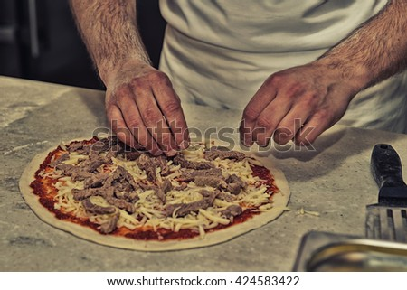 Making of a meat pizza in a restaurant, toned image - stock photo