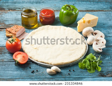 Making of pizza original set including tomatoes, mushrooms, cheese, arugula, ketchup and olive oil all placed on blue aged wooden surface - stock photo