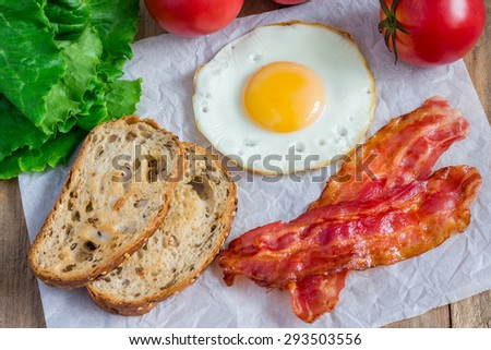 Making open face sandwich with egg, bacon, tomato and lettuce - stock photo