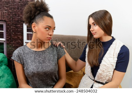 Making peace. A beautiful young girl friend saying she is sorry to her friend while sitting in the cafe - stock photo