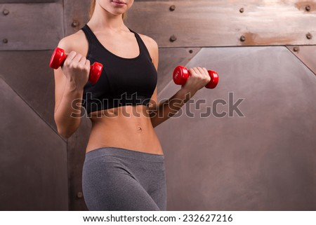 Making perfect biceps. Close-up of muscular young woman holding dumbbells  while standing against metal background  - stock photo