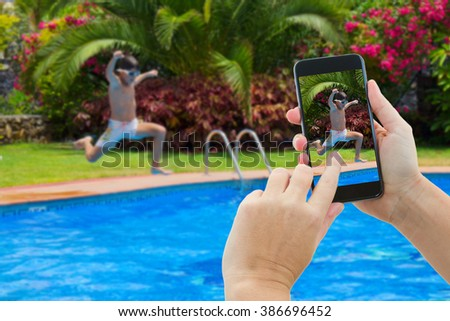 making photo of boy jumping in water of swimming pool - stock photo