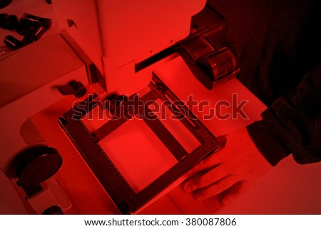 Making  photo using the old photographic enlarger. Frame the corrective image with red light lamp. - stock photo