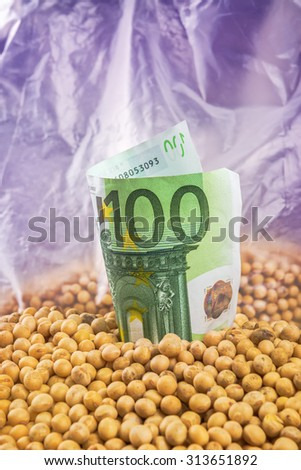 Making profit in agriculture business from soybean cultivation - soya bean plant, pods and beans harvested in late summer from cultivated field with Euro banknotes, selective focus - stock photo