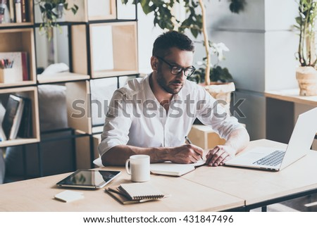 Making some notes. Concentrated mature man writing something in note pad while sitting at his working place in office  - stock photo