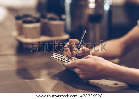 Making some notes. Part of close-up of young woman writing in notebook while standing at bar counter - stock photo