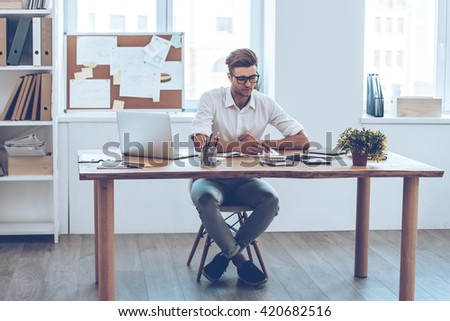 Making some notes. Pensive young handsome man writing in his notebook while sitting at his working place - stock photo
