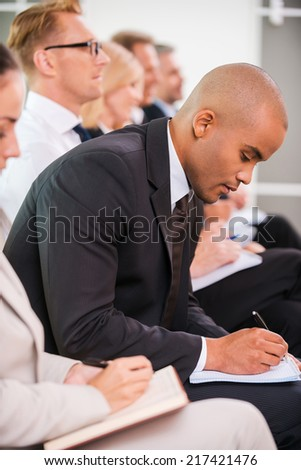 Making some urgent notes. Side view of business people writing something in their note pads while sitting in a row
