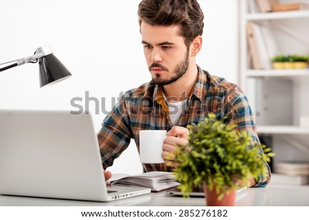 Making sure all the task get down. Confident young man working on laptop and holding cup of coffee while sitting at his working place - stock photo