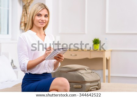 Making the list. Attractive young woman sitting at the edge of bed in her hotel room and busy writing a list.  - stock photo