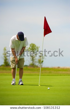 Making the shot on the Green. Ball dropping in Hole. - stock photo