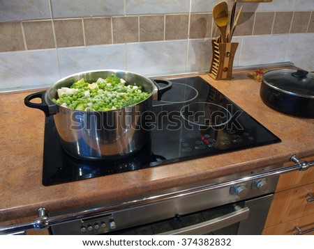 Making vegetable stew in stainless steel pot on ceramic surface of electric stove.