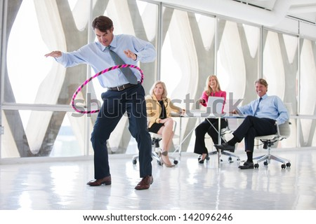Making work fun a Group of Mature Adults taking a play Break in a modern office to get ideas flowing - stock photo