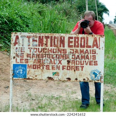 MAKOUA, CONGO, AFRICA - SEPTEMBER 27: Journalist and sign warns visitors that area is a Ebola infected. Signage informing visitors that it is a ebola infected area. September 27, 2013,Congo, Africa.   - stock photo