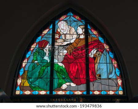 "MALACCA, MALAYSIA - DEC 20, 2013: Stained Glass Window ""Jesus, Martha and Mary"" of Church of St. Francis Xavier. Malacca City is the capital city of the Malaysian state of Malacca.  - stock photo"