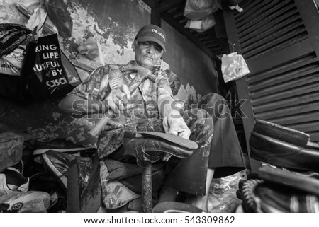 MALACCA, MALAYSIA, DECEMBER 24 2016: Unidentified shoe repairman repairing shoes at his street workshop
