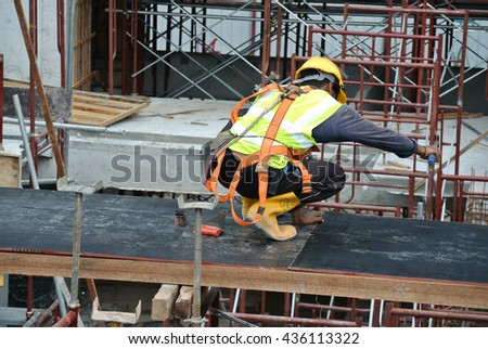MALACCA, MALAYSIA -MAY 25, 2016: Construction workers fabricating timber form work made from plywood and wood at the construction site in Malacca, Malaysia.