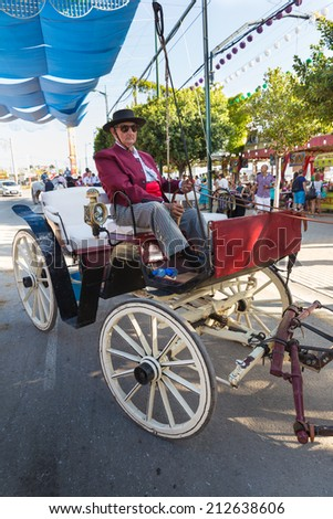 MALAGA, SPAIN - AUGUST 21, 2014: Coachman with one of the oldest carriages in town at Malaga August Fair - stock photo