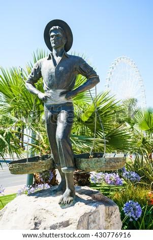 MALAGA,SPAIN - 28 MAY 2016: Cenachero statue of fisherman against of plants and blue sky - stock photo