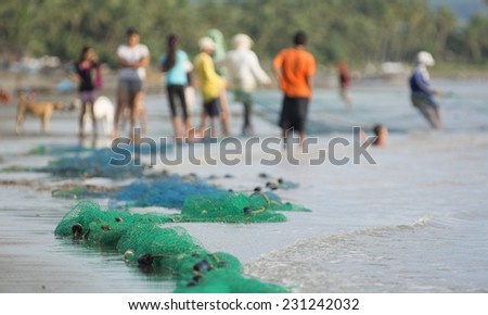 Malandog, Philippines - October 22, 2014: People netting from the beach caching small fish to share with the community living on Datu sumakwel beach - stock photo
