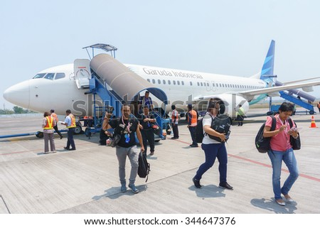 Malang Indonesia - Oct 12, 2015:Passengers exiting Garuda Indonesia aircraft  parked at Abdul Rachman Airport in Malang.This airport is among main hub to highland of East Java Indonesia. - stock photo