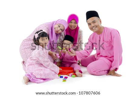 malay family in traditional malay clothing - stock photo