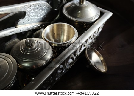 Malay heritage brassware, wedding equipment called Tepak Sireh over wooden background. shoot in low light and selective focus
