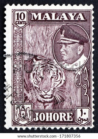 MALAYA - CIRCA 1960: a stamp printed in Malaya shows Tiger with Portrait of Sultan Ismail, circa 1960 - stock photo