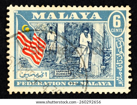MALAYA - CIRCA 1959: Blue color postage stamp printed in Federation of Malaya with illustrative image of rubber tappers and Federation of Malaya flag. - stock photo