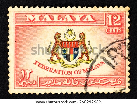 MALAYA - CIRCA 1956: Red color postage stamp printed in Federation of Malaya with illustrative image of the Federation of Malaya coat of arms. - stock photo
