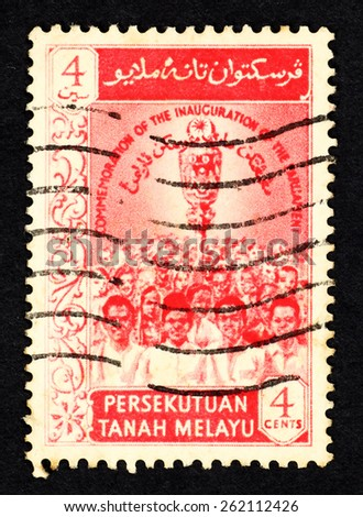 MALAYA - CIRCA 1957: Red color postage stamp printed in Federation of Malaya with image of Parliament members to commemorate the inauguration of the Malaysian Parliament. - stock photo