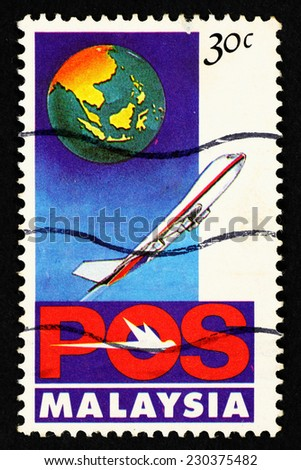 MALAYSIA - CIRCA 1992: Postage stamp printed in Malaysia with image of an airplane and a globe with Malaysia map. - stock photo