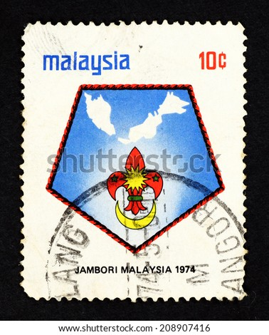MALAYSIA - CIRCA 1974: Postage stamp printed in Malaysia with image of Boy Scout emblem against the Malaysian map to commemorate the 3rd Malaysia Jamboree in Johor. - stock photo
