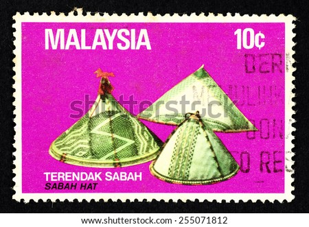 MALAYSIA - CIRCA 1982: Purple color postage stamp printed in Malaysia with image of the Sabah Hat known as Terendak Sabah. - stock photo