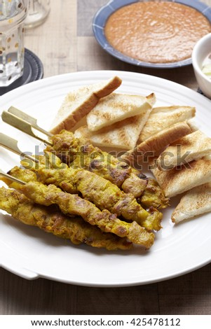 Malaysian chicken satay with delicious peanut sauce, one of famous local dishes. - stock photo