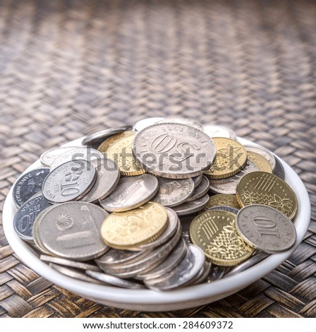 Malaysian coins in a white bowl over wicker background