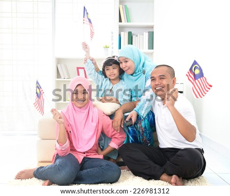 malaysian family celebrating while watching television over a tournament , some are carrying country flags  - stock photo