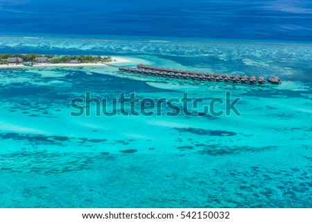 Maldives beach from birds eye view. Aerial view on Maldives island, Ari atoll. Tropical islands and atolls in Maldives from aerial view. Summer holiday beach landscape background in Maldives.