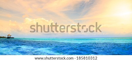 Maldives bungalows sunset panorama. beautiful view of the ocean - stock photo