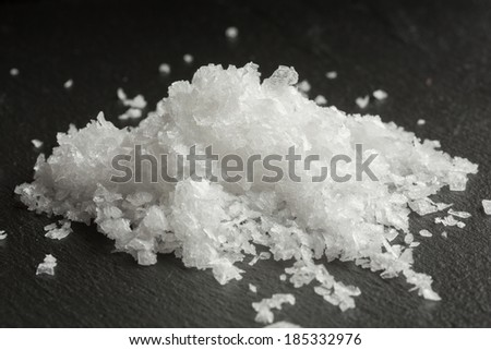 Maldon sea salt on black background - stock photo