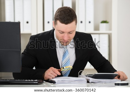 Male accountant analyzing invoice with magnifying glass at desk in office - stock photo
