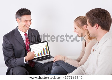 Male Advisor Showing Graph On Laptop Screen To Young Couple - stock photo