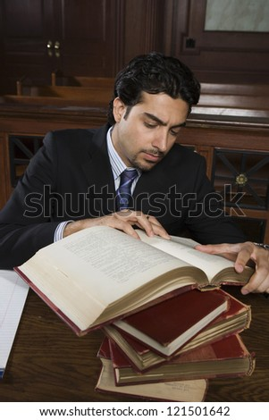 Male advocate taking reference from book while sitting in courtroom - stock photo