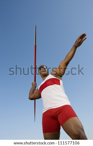 Male African American athlete throwing javelin - stock photo