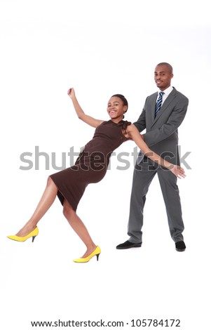 Male African American business manager in suit and tie, catching a female colleague wearing a brown dress and yellow shoes, in a trust exercise for bonding and team work in office - stock photo