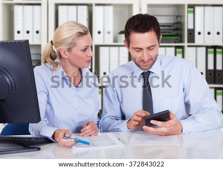 Male and female accountants calculating finance together at desk in office