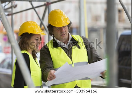 Male and female architects checking blueprints among scaffolding on construction site
