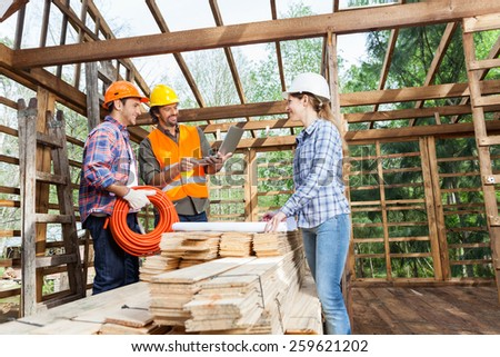 Male and female architects working in incomplete wooden cabin at site - stock photo